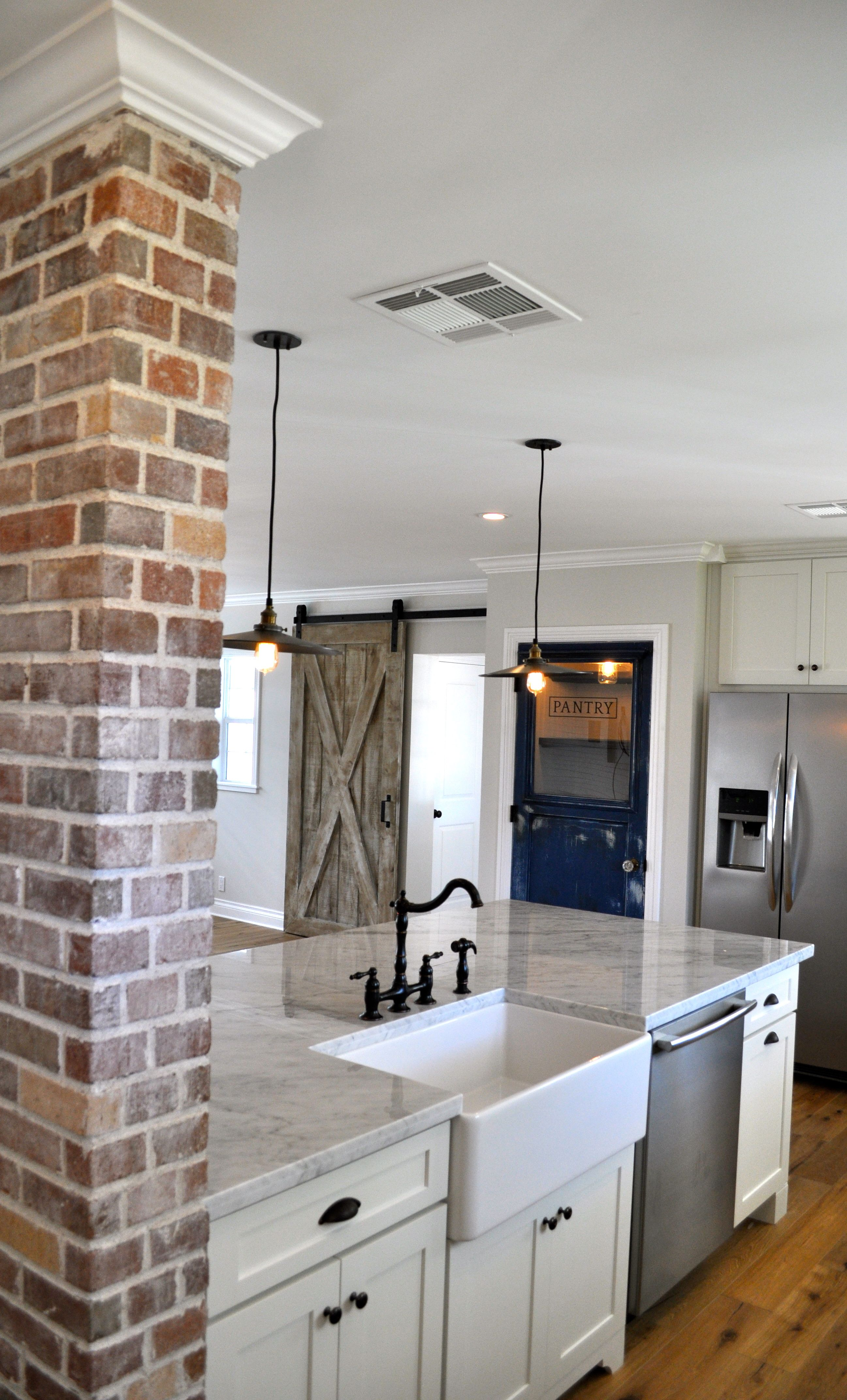 wall color  brick accent wall  marble tops. Open brakfast bar with furniture base legs and custom brick