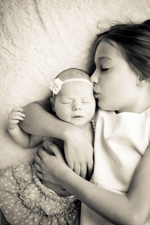 sisterly love, big sister kissing newborn baby girl, warm toned ...