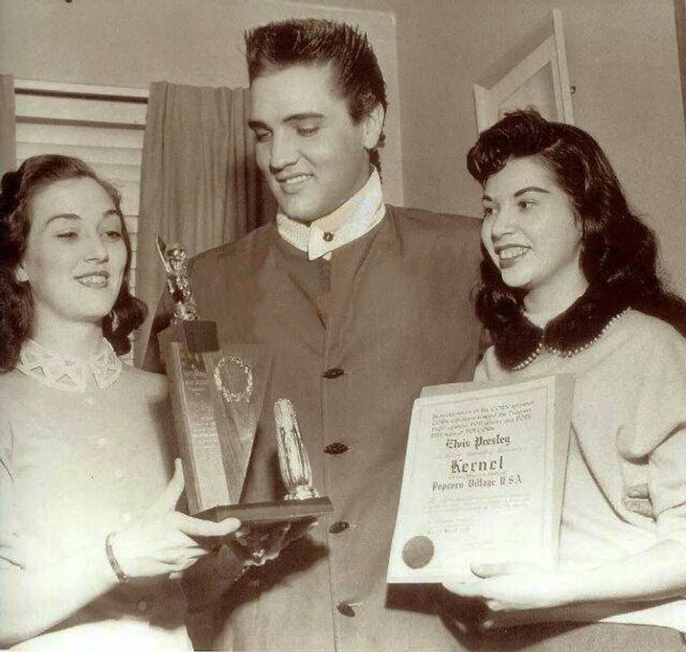 """The 1958 photo was taken at the home of Gene (Elvis' cousin) and Louise Smith on March 20-1958. Arlene Cogan had gone to visit them and suddenly Elvis arrived on his motorcycle in the pouring rain. The plaque read in part """"In recognition of his CORN-spicious CORN-tribution toward the Progress, PrOPagation, POP-ularity and POPS-RITE-ness of POPCORN ..."""" and was dated March 19. The story can be read in the book """"Elvis, This One's For You"""" by Arlene Cogan."""