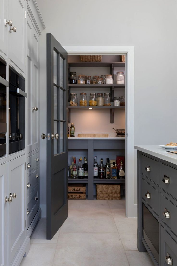 This open plan kitchen in Ingatestone has the perfect walk in pantry. Hidden behind a Georgian style door painted in H M Top Hat, the pantry conceals masses of open storage just off of the main kitchen.