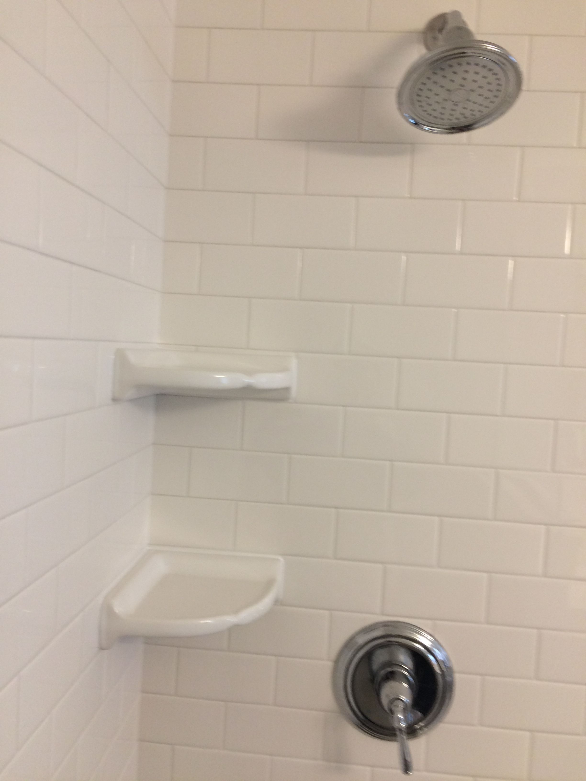 Corner Shelves With Subway Tile In Shower And White Grout