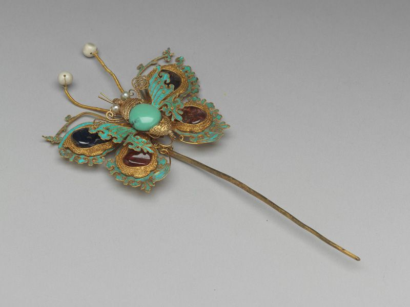 Gold Hairpin with a Butterfly-shaped Finial in Filigree Early Qing period Gold, rubies, sapphires, turquoise, Oriental Pearls, and kingfisher feathers Overall length: 17.3 cm, width: 8.5 cm National Palace Museum Colelction