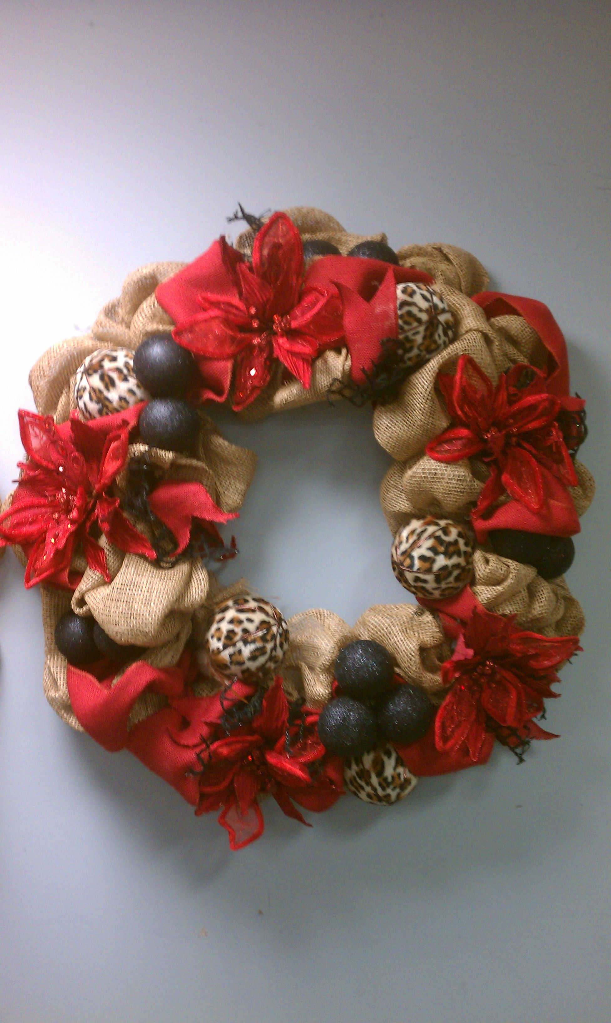 """Burlap wreath with poinsettas and leapard print ornaments. Aprox. 30"""" wide."""