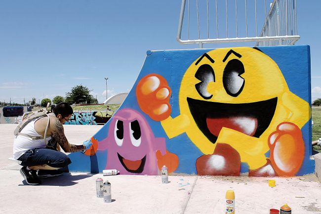 Joseph Montoya spray painted a Pac-Man mural on the side of a ramp at Washington Skate Park on Saturday. Community members helped Alamogordo Club for Teens