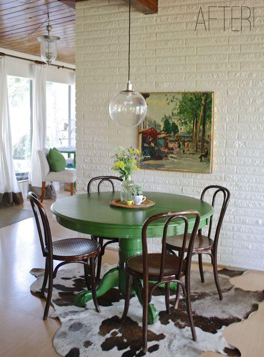Comedor. mesa redonda de madera en verde. pared de ladrillo en ...
