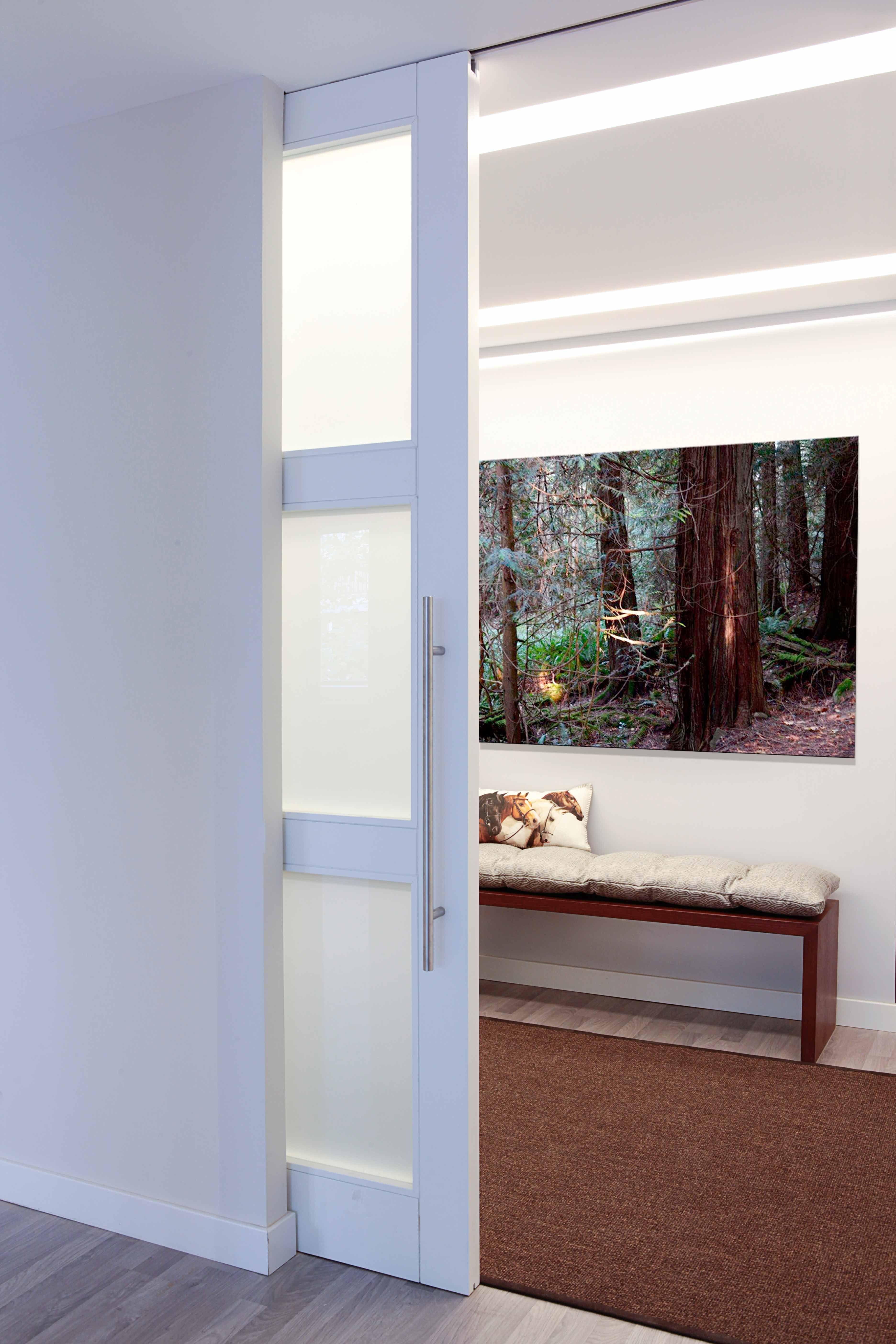 puerta corredera de suelo a techo e iluminacion oculta en el techo para una entrada