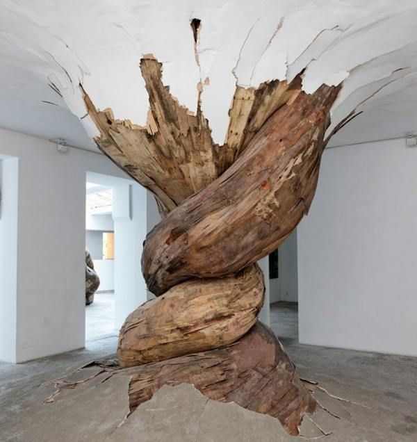 """Trees Burst Through Gallery Walls and Ceilings  Brazilian artist Henrique Oliveira's powerful recycled wood art installations snake through their exhibition spaces like massive living trees that burst out of walls and through ceilings. Oliveira scours the streets of Sao Paulo to gather plywood, which he then separates into layers and combines to create his massive """"tridimensionals"""" sculptures. The stunning mixed media pieces are a combination of sculpture, painting and architecture."""