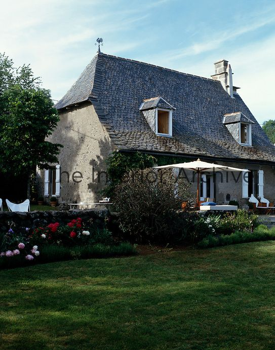 The Steeply Sloping Roof Of This Old House Is Covered In Weathered Grey  Tiles   Auvergne