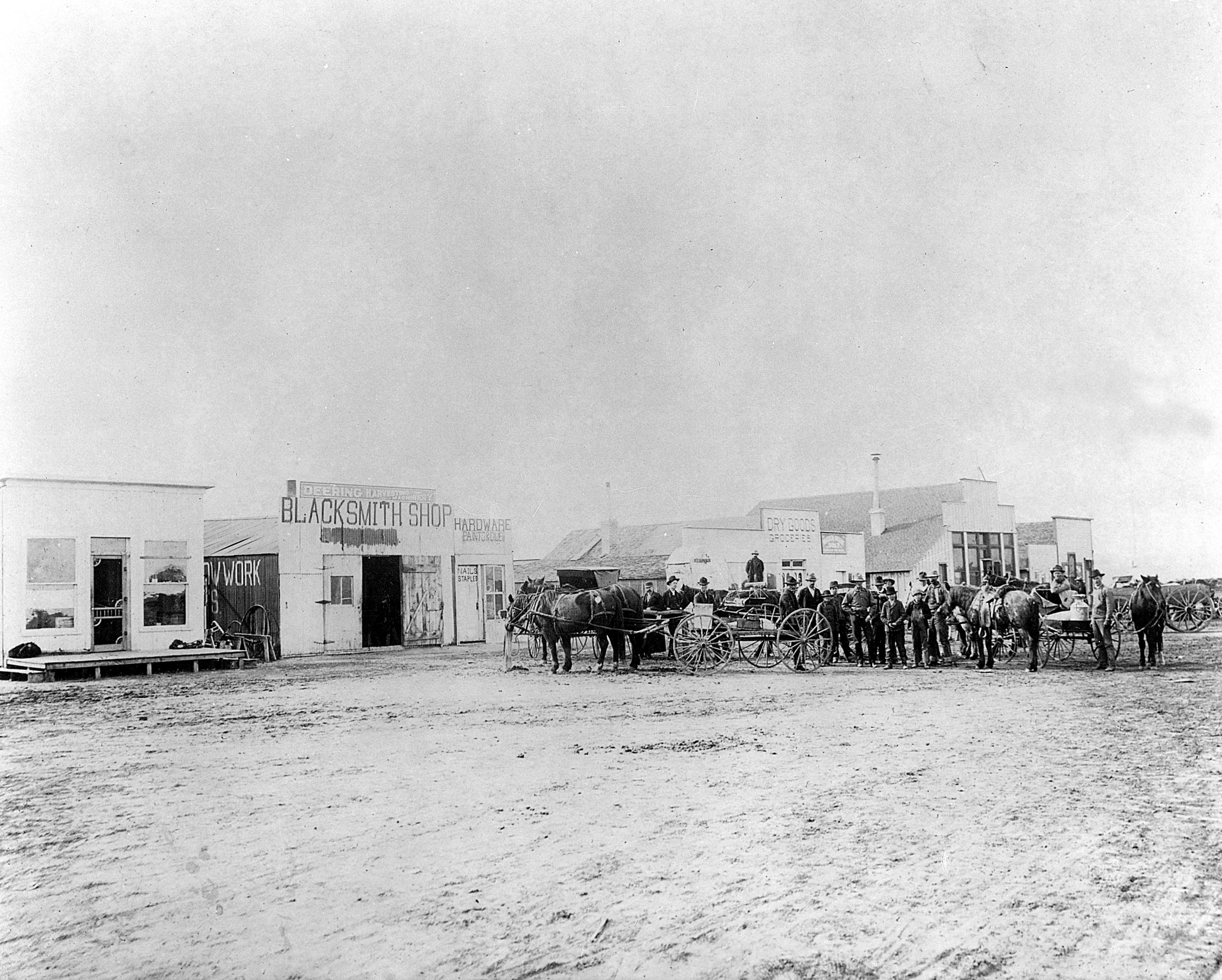 Euclid Avenue Looking Southwest c 1903 From left to right the structures situated on the south side of Euclid Avenue today's Mainstreet are the old Hoffman Foster Meat Market the Nicoli Blacksmith Shop A Amos General Store Walter Lewis General Merchandise Store and the Oswald Shoe Store The blacksmith shop was torn down not long after this picture was taken and in 1910 Jim New b built his barber shop on the site The barber shop would be e a long time Parker post office