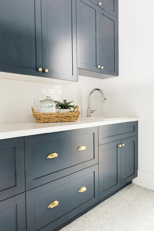 Navy Blue Laundry Room Features Shaker Cabinets Adorned With Brass Cup Pulls Paired