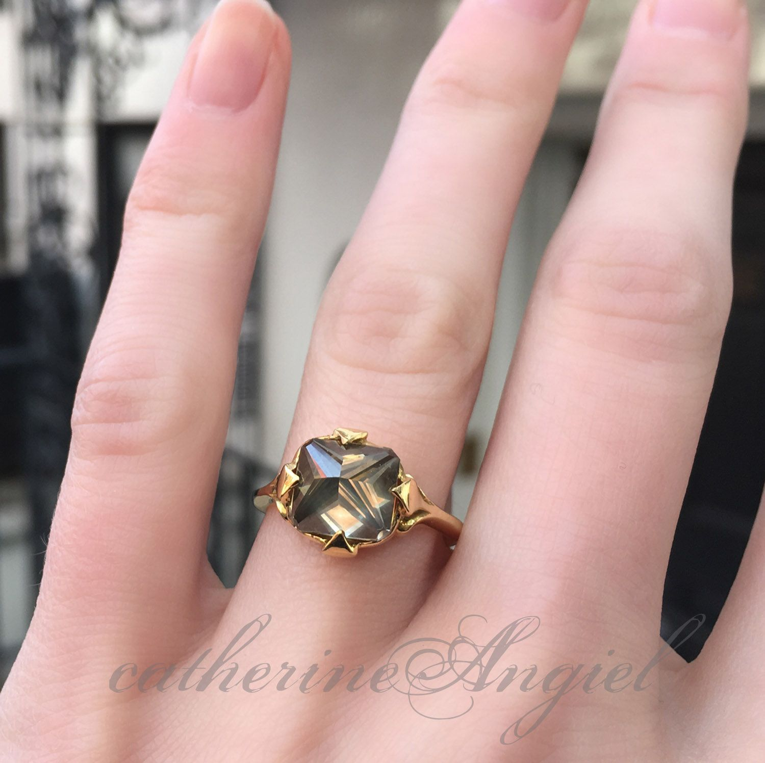 An inverted grey diamond set in a hand crafted, yellow gold ...