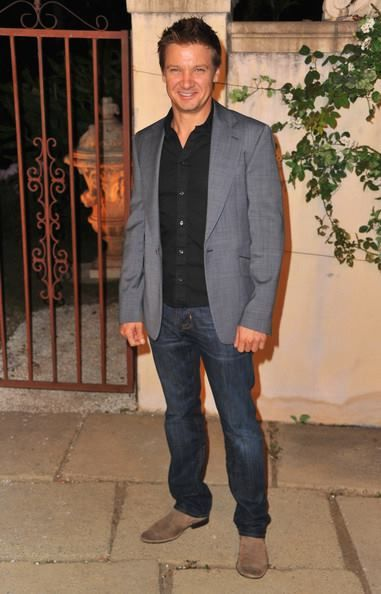 Jeremy Smiling and Wearing a Black Open-Necked Button-Up Shirt, Blue Jeans, Gray Suit Jacket and Suede Boots Standing in Front of Metal Gate
