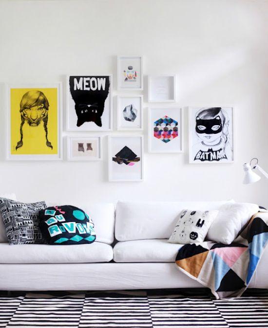A sala ficou com um toque moderno por causa dos quadrinhos , almofadas estampadsa e tapete de listras