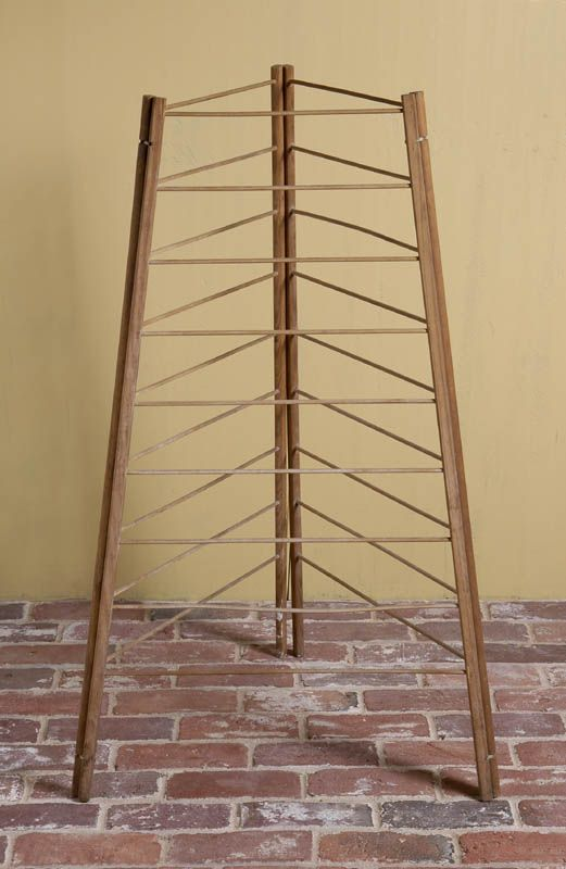 "Herb dryer, maple and pine, original finish, three-section rope hinged drying rack, six rectanglar upright poles with nine delicately turned rails graduated from top to bottom, used in a triangular configuration for drying, can be folded flat for storage, 41"" h, 12"" w, 15"" d."