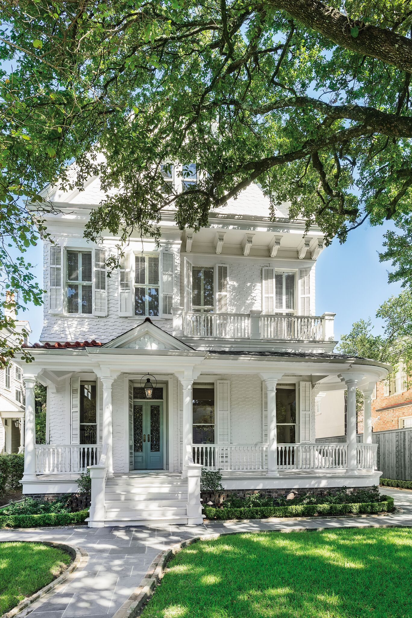 Stately white painted Victorian home has breathtaking architecture and curb appeal in the lower Garden District of New Orleans.