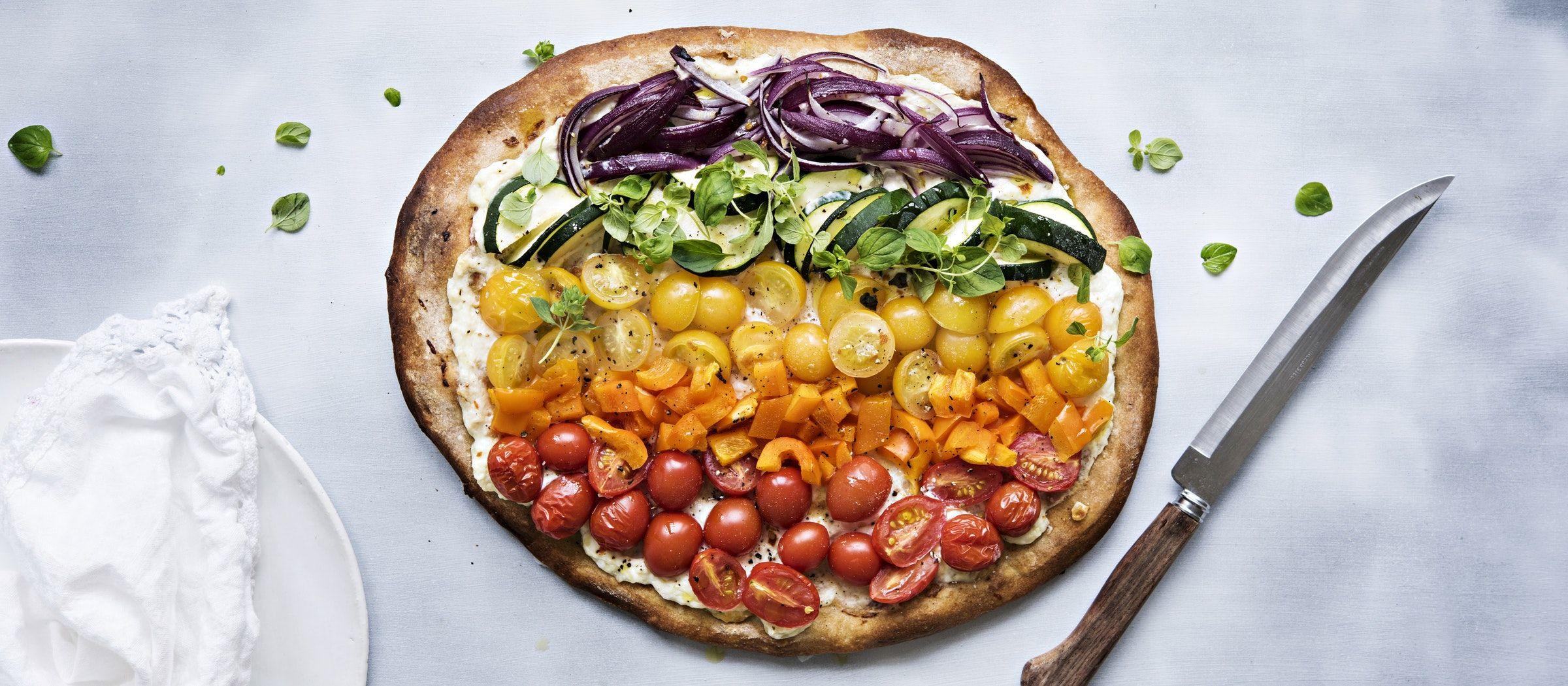 Värikkäistä kasviksista syntyy hauska sateenkaaripizza, kun asettelet ne ratoina ricottajuusto-mozzarellaseoksella sivellyn pizzan päälle.