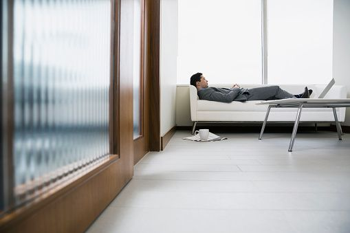 Businessman laying on sofa in office