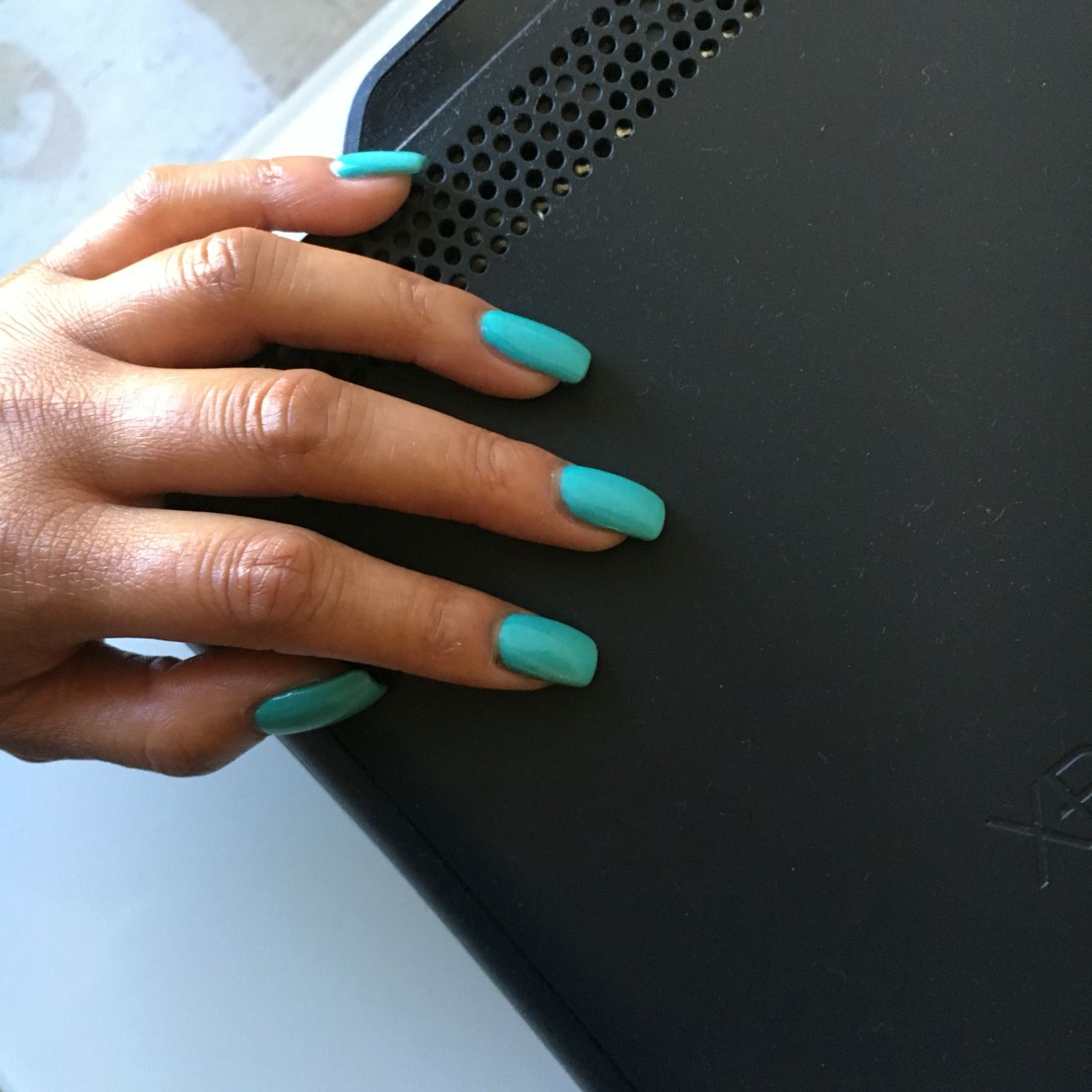 Squoval shaped acrylic gel nails in cyan