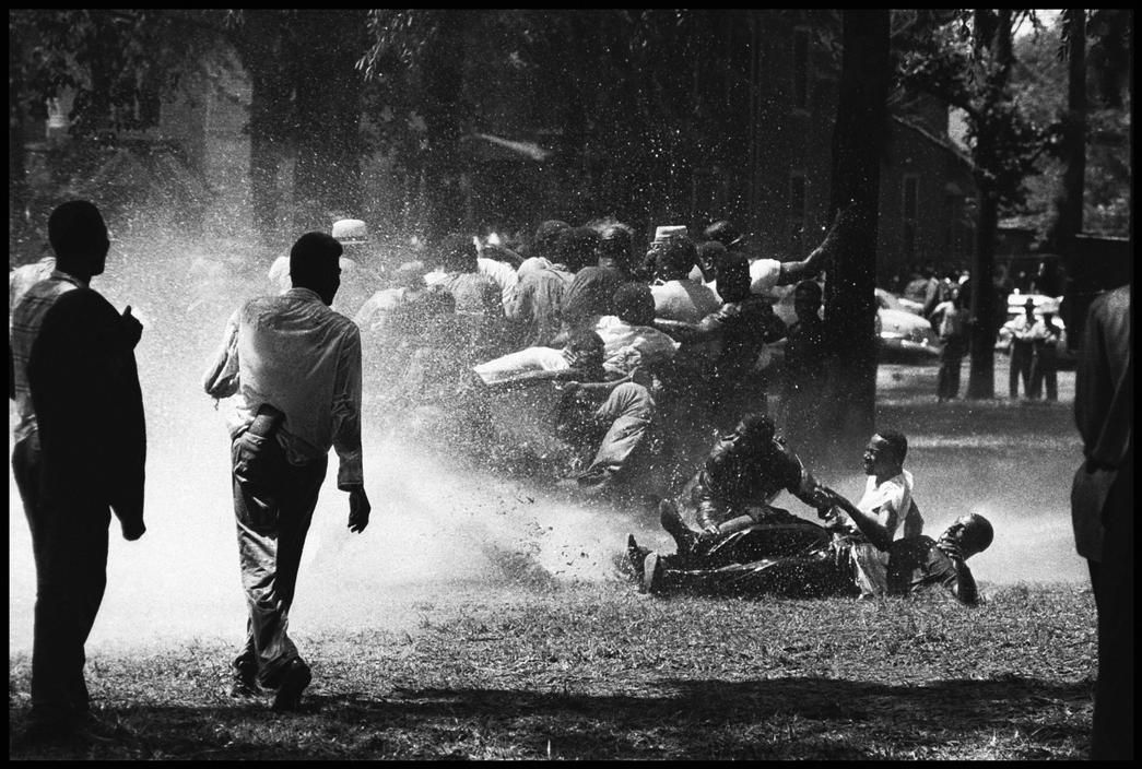USA. Alabama. Birmingham. 1963. Firemen turn high-powered hoses capable of stripping bark from trees against peaceful demonstrators, who are knocked down and skid across the grass in Kelly Ingram Park. By coming together and holding on to one another, they are able to stand up to the fire hoses. When they could no longer knock down the united protestors, the fireman turned off their hoses. (Bob Adelman)