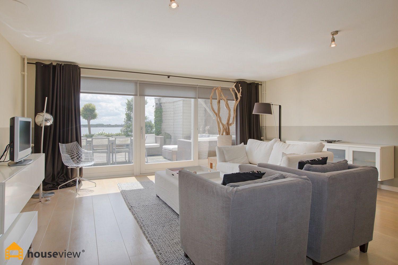 Prachtige living met witte hoogglans meubels en uitzicht op de