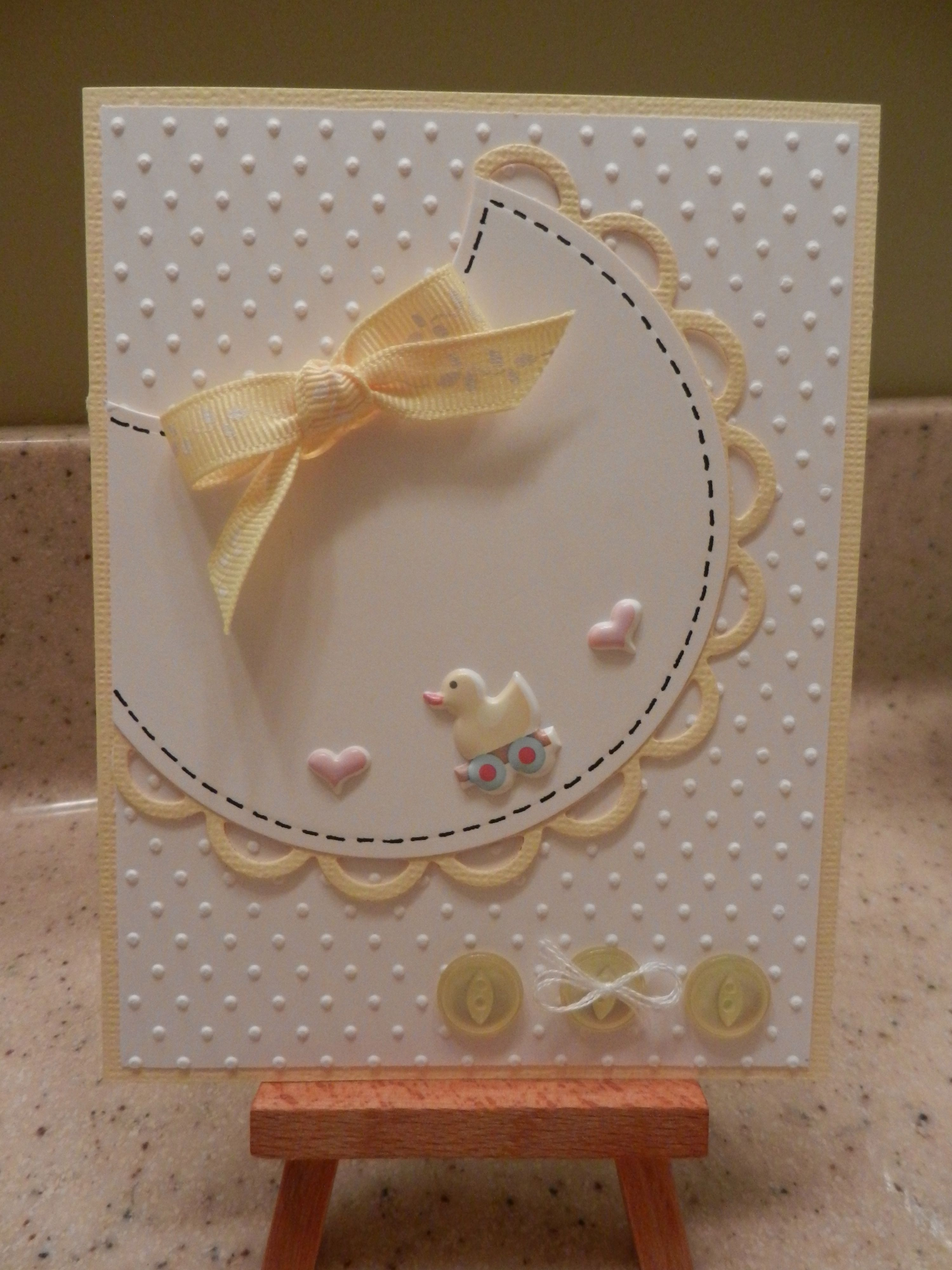 Cut this adorable bib from a circle, with a scallop punch edging in your color of choice. Add a bow and duck or other embellishments, and place the whole thing on top of swiss dotted paper. Buttons tied with twine finish off this great handmade baby card.                                                                                                                                                     More