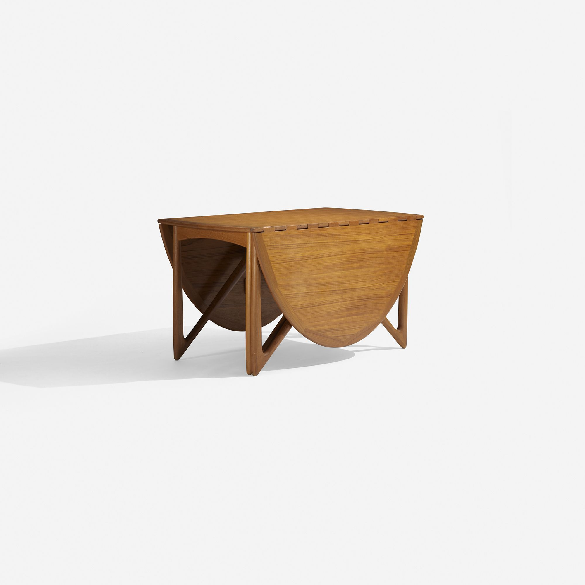 Lot 105: Kurt Ostervig. drop-leaf dining table. c. 1960, teak. 77 w x 51 d x 28½ h in. result: $2,500. estimate: $3,000–5,000. Table features two 24-inch drop-leaves; table measures twenty-nine inches when folded.