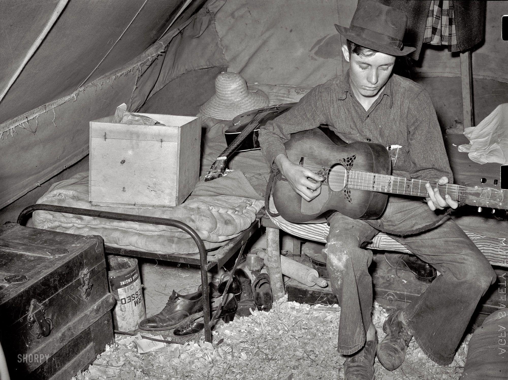 White migrant strawberry picker playing guitar in his tent near Hammond, Louisiana, 1939