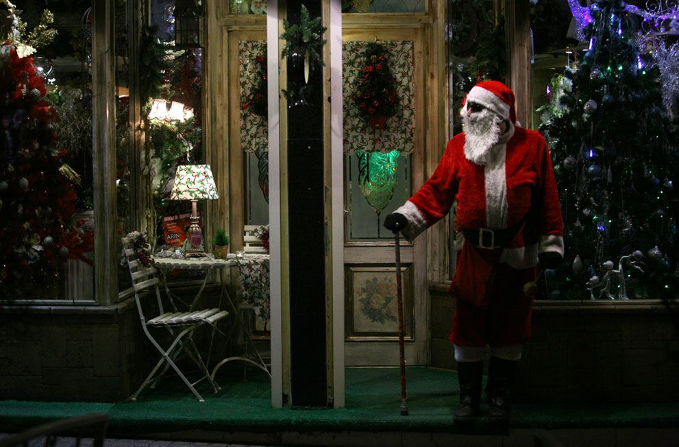 An Iranian man wears Santa Claus costume, as he stands in front of a shop with Christmas decorations, in central Tehran