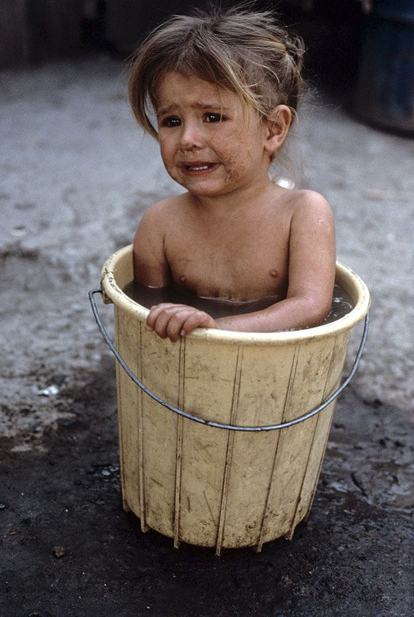 A young Mennonite farm girl takes a bath in a bucket at home in ...