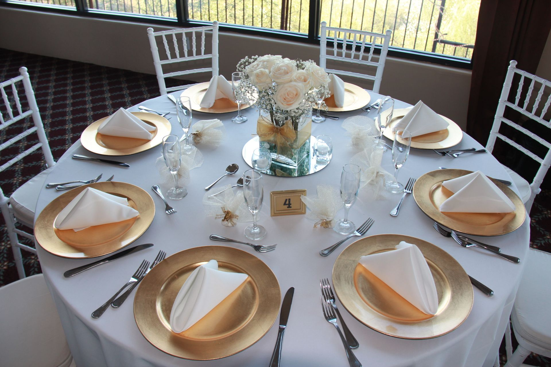 Gold charger plates with white table linen and napkins