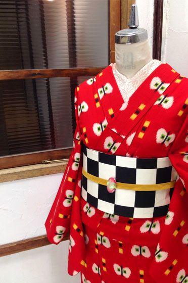 綺麗な赤色に、蝶々のような、半分に切ったリンゴのようなモチーフが織り出されたレトロポップなウールのアンサンブル(羽織と着物のセット)です。