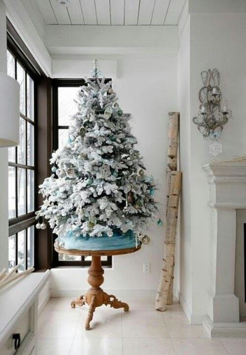 a smaller flocked tree on a small table a great way to gain some height without being more to decorate also a good way to keep small kids pets from