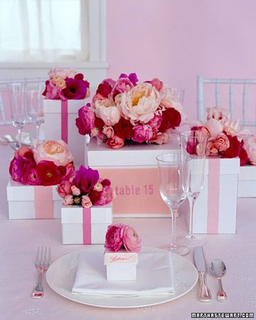 Boxes topped with flowers make a beautiful centerpiece; a table number is embroidered onto ribbon encircling the largest box. Inside, the stems sit in water bottles stabilized by crumpled paper. Favor boxes, which contain nonpareils, double as place cards.