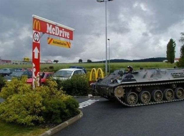 People driving armored military vehicles