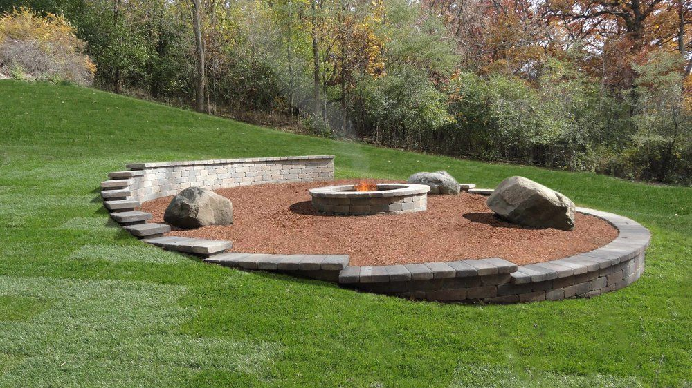 Natural fire pit area built into a slope garden for Making a fire pit area