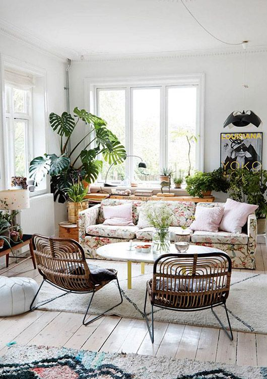 Great boho inspired living room with a floral couch rattan chairs and lots of green plants for Urban boho style living room