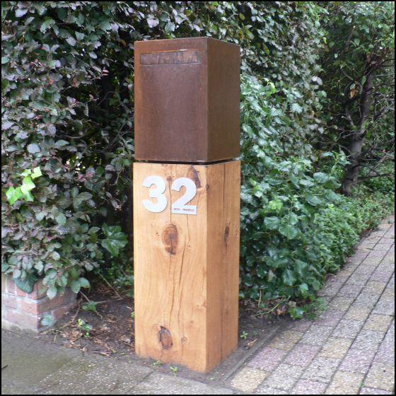 Brievenbus hout cortenstaal. Onderaan is een sokkel in hout met daarop een brievenbus met een klep in cortenstaal.