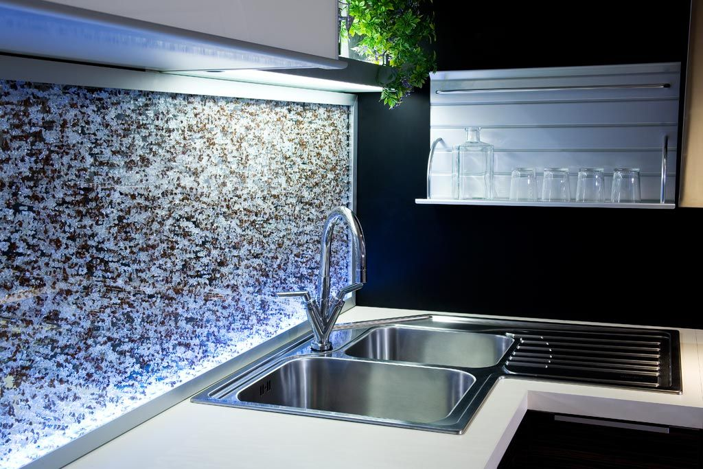 Glasrückwand, bestehend aus einzelnen Steinchen hinter einer ...