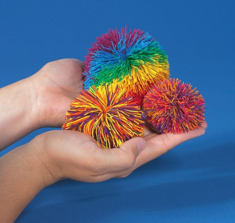Someone holding several koosh balls
