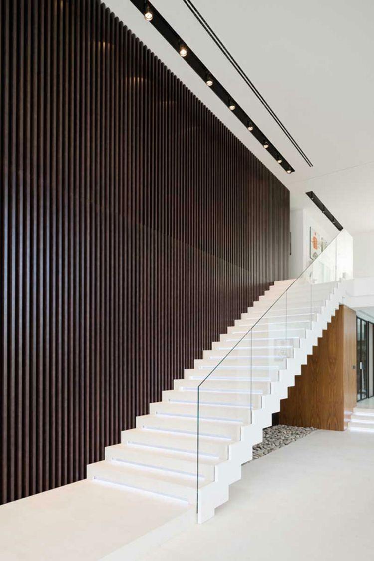 die minimalistische treppe wird durch eine dunkle wand aus holzleisten hervorgehoben treppen. Black Bedroom Furniture Sets. Home Design Ideas