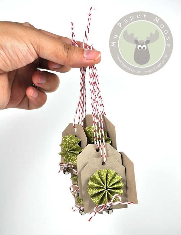 Super simple Christmas gift tags using paper rosettes, baker's twine, and mini jingle bells.
