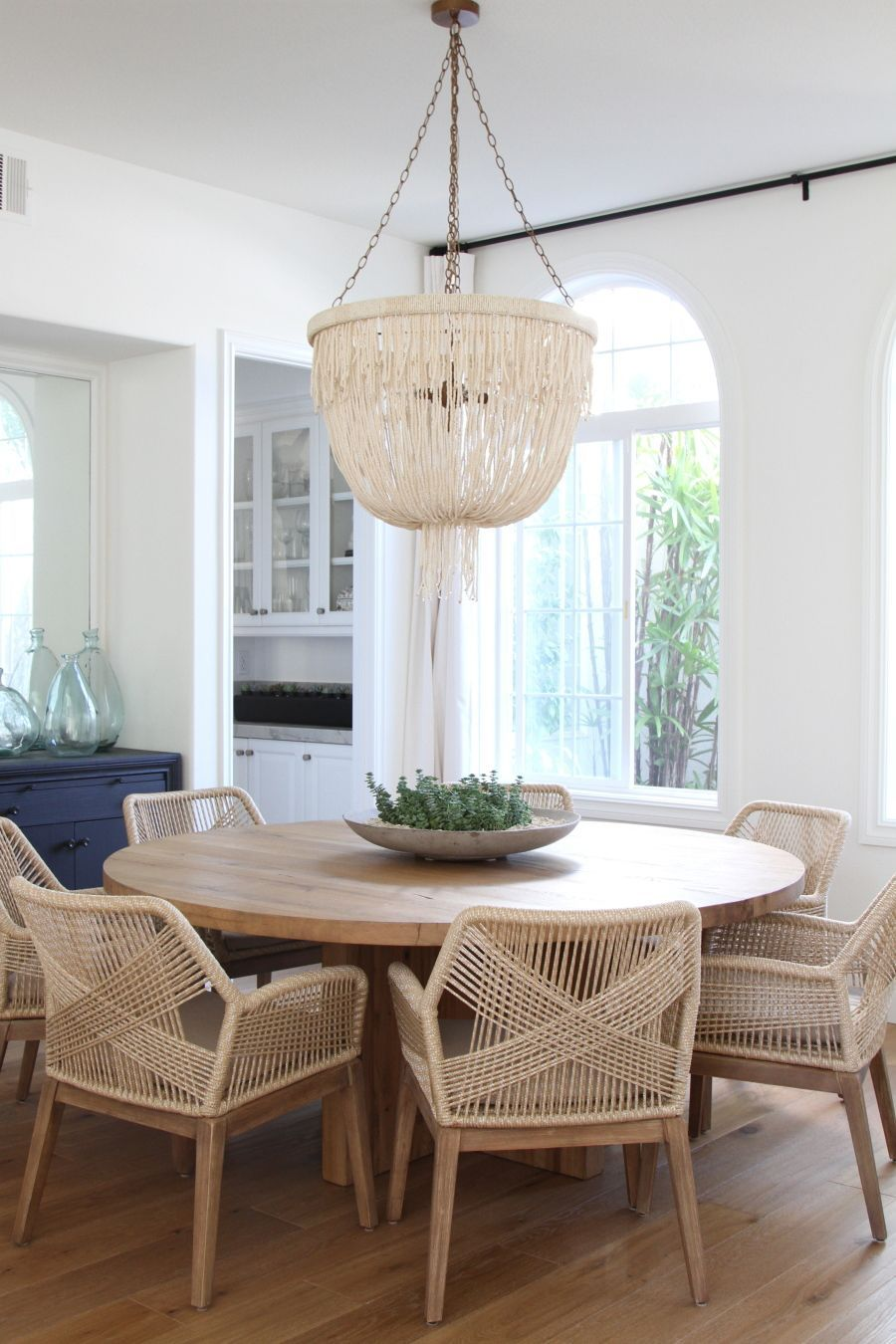 beaded chandelier and woven chairs flank a rounded wood dining table ...