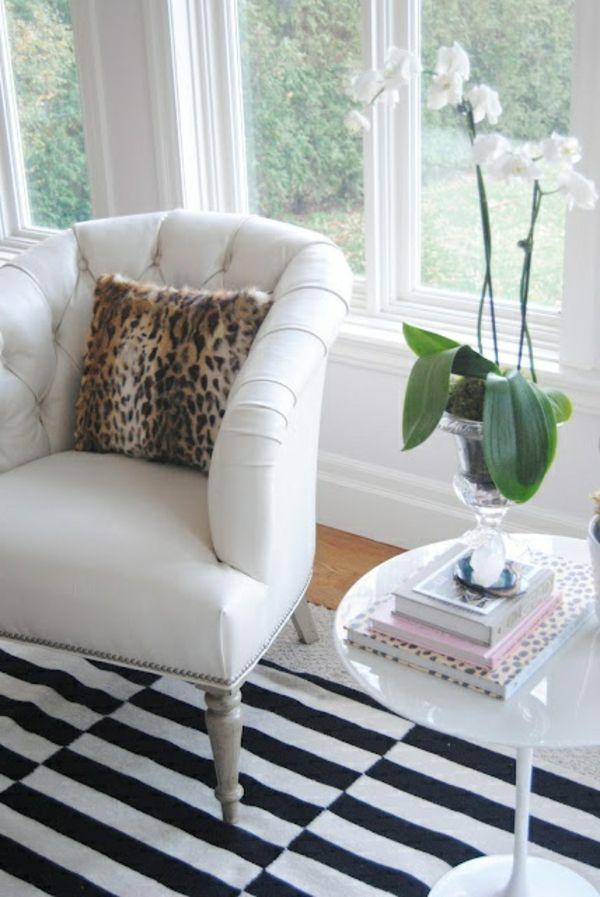 wohnzimmer mit einem weißen sessel, weiße blumen, dekokissen leopard ...