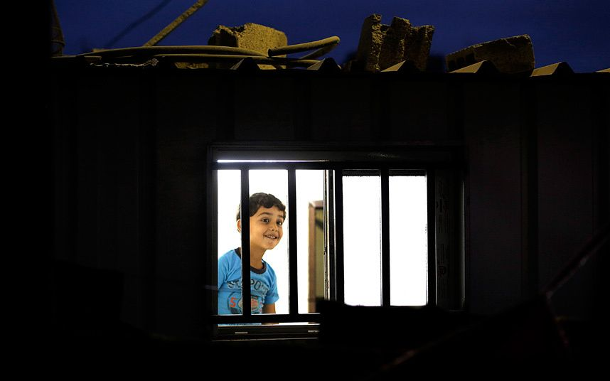 Six-year-old Mohammed Al Za-aneen looks from the window of his family's temporary housing next to their destroyed house, which was damaged during the Israeli war against Gaza in the summer of 2014, in the east of Beit Hanun town in the northern Gaza Strip. More than 100,000 Palestinians remain homeless one year after the 2014 summer Israel-Gaza war.