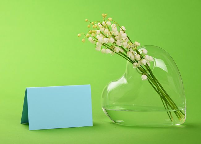 Bunch Of Lily Of The Valley Convallaria Majalis Flowers In Heart Glass Vase With Blue Card On Green Flower He Holiday Templates Love Massage Valentine Poster