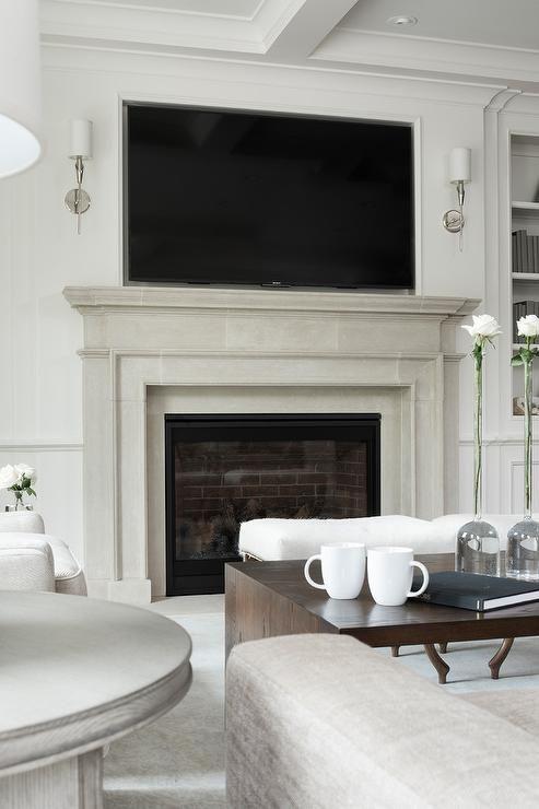 Light Gray Limestone Fireplace With Mantel Showcasing A Tv