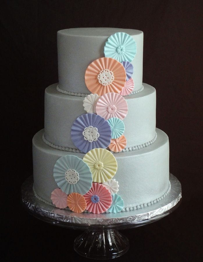 cascade of pastel gumpaste rosettes on light grey buttercream the bride made a backdrop for the cake table with pastel colored paper rosettes - Wedding Cake Design Ideas