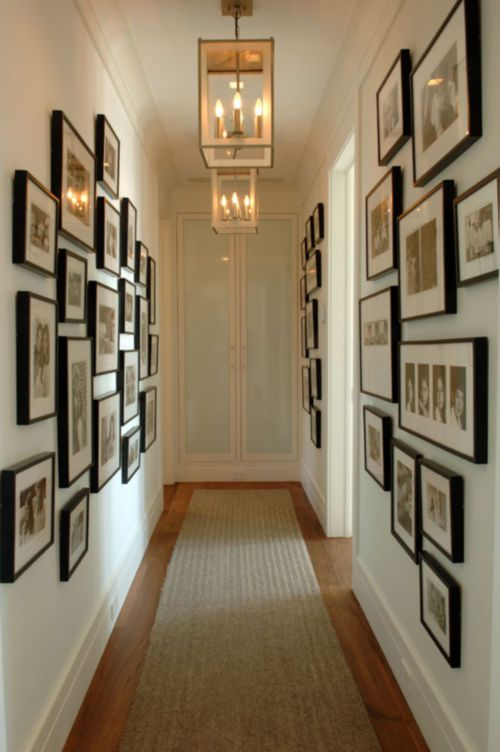 Narrow hallway with black picture frames on the walls ...