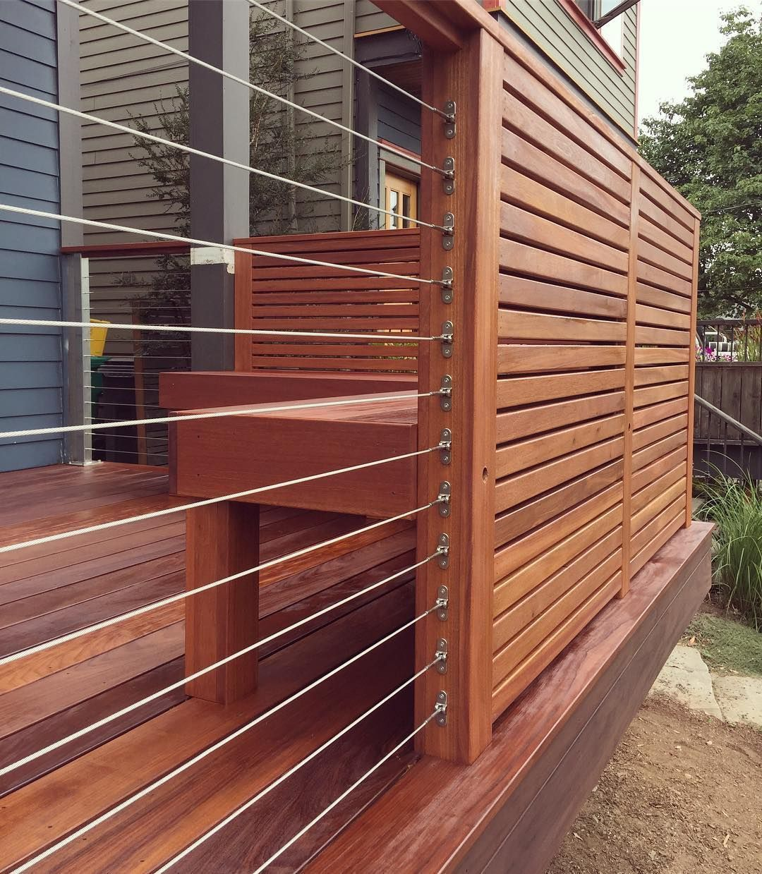 The stainless steel railing cable transitions great into a privacy screen with a bench behind itcedarfence The stainless steel railing cable transitions great into a priv...