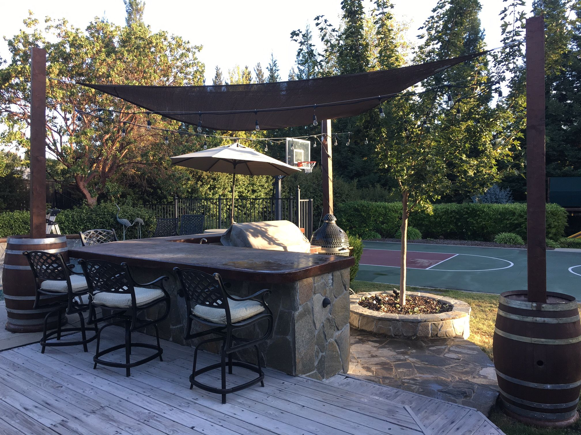 shade sail attached to wine barrels in outdoor bar area doing